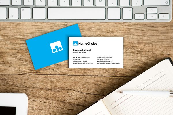 HomeChoice business card design front and back on desk with keyboard and notebook