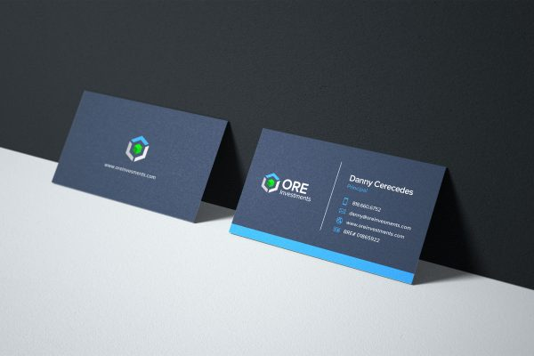 ORE Investments business card designs leaning on a wall